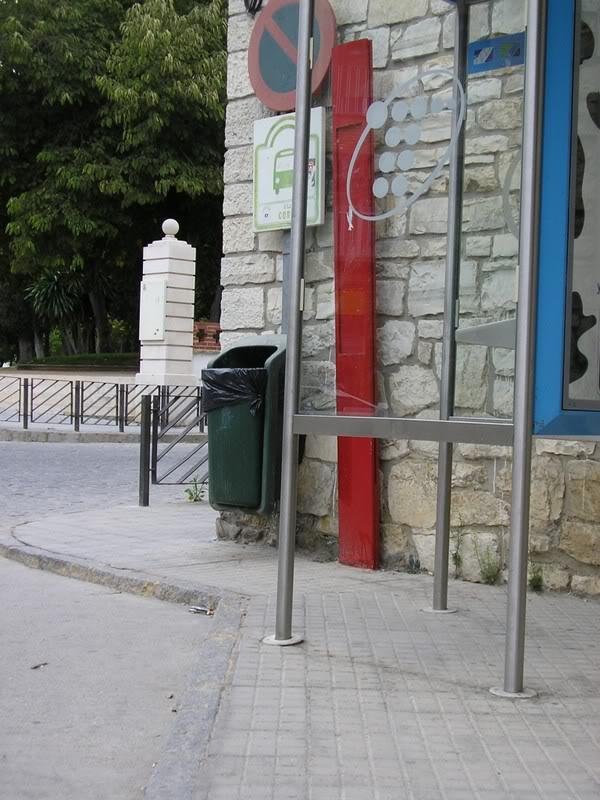 Acera junto al apeadero de autobuses, ocupada por una cabina de teléfonos