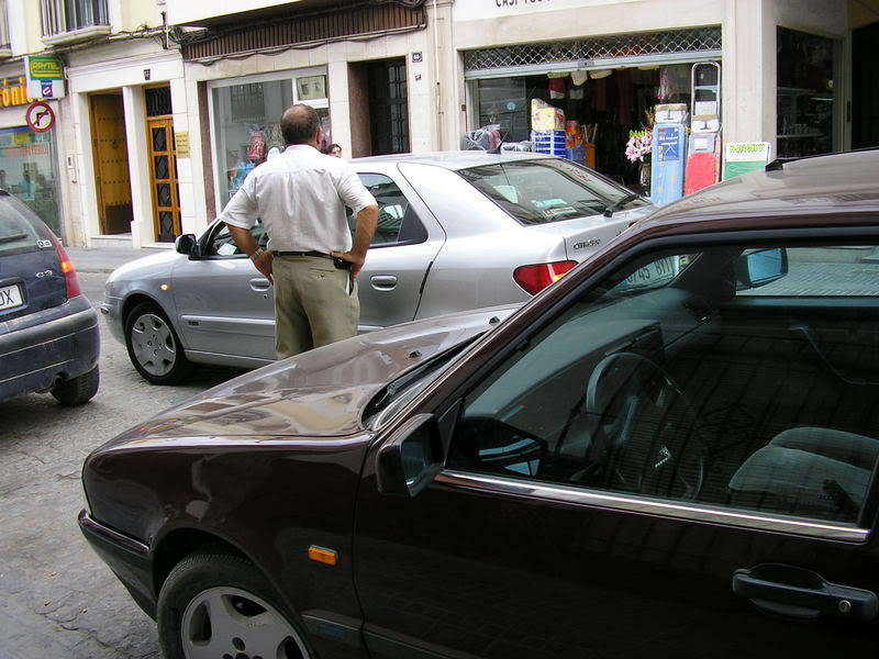 Coche en doble fila en la calle Puerta de Aguilar, con hombre con brazos en jarras